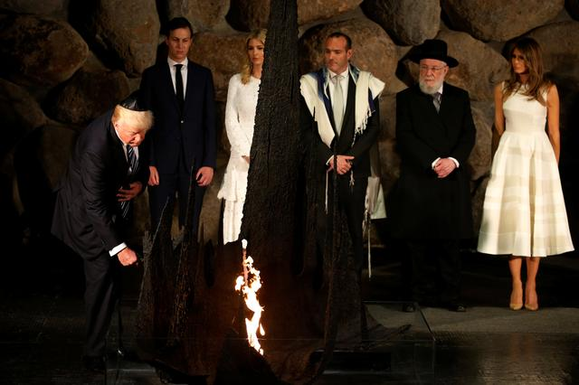 U.S. President Donald Trump rekindles the eternal flame during a ceremony commemorating the six million Jews killed by the Nazis in the Holocaust, in the Hall of Remembrance at Yad Vashem Holocaust memorial in Jerusalem May 23, 2017.  REUTERS/Jonathan Ernst
