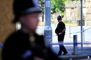 Police officers stand on duty at the cordon surrounding the Manchester...