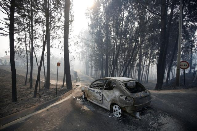 A burned car is seen in the aftermath of a forest fire near Pedrogao Grande, in central Portugal, June 18, 2017.  REUTERS/Rafael Marchante