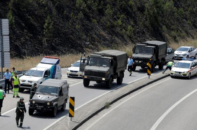 Army vehicles drive on the IC8 motorway on their arrival for helping during a forest fire near Pedrogao Grande, in central Portugal, June 18, 2017.  REUTERS/Miguel Vidal