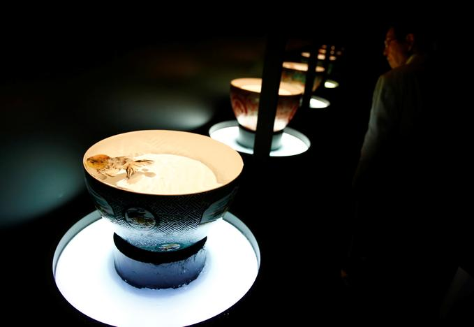 A man looks at an installation that uses goldfish in illuminated bowls at the Art Aquarium exhibition in Tokyo, Japan. Kim Kyung-Hoon