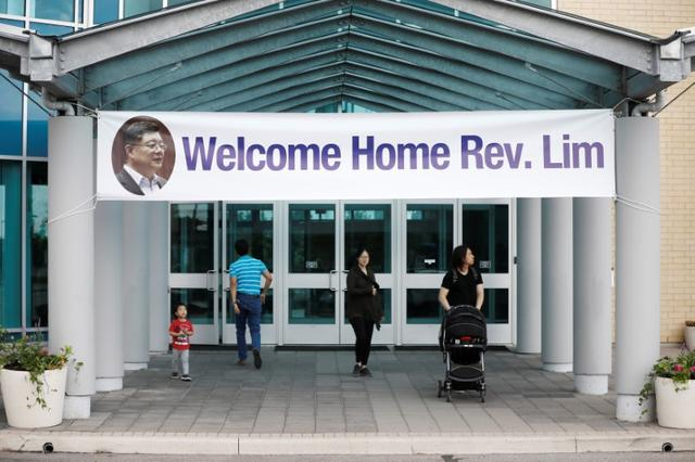 People walk under a welcome home sign for Pastor Hyeon Soo Lim, who returned to Canada from North Korea after the DPRK released Lim on August 9 after being held for 31 months, at the Light Presbyterian Church, in Mississauga, Ontario, Canada August 12, 2017. REUTERS/Mark Blinch