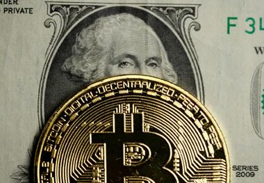 FILE PHOTO: A Bitcoin and dollar note are seen in this illustration picture