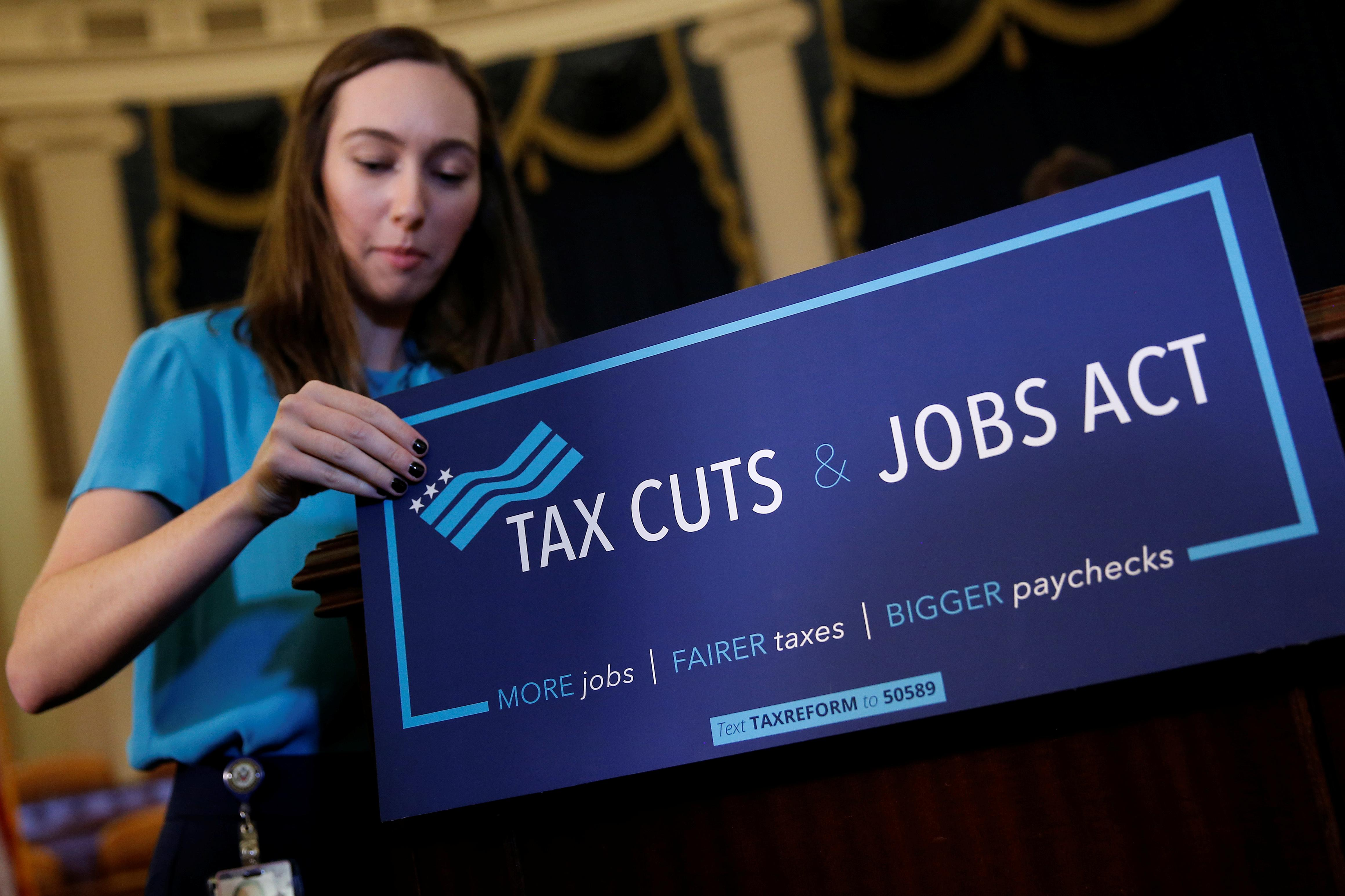 A congressional aide places a placard on a podium for the House Republican's legislation to overhaul the tax code on Capitol Hill in Washington, U.S., November 2, 2017.   Joshua Roberts
