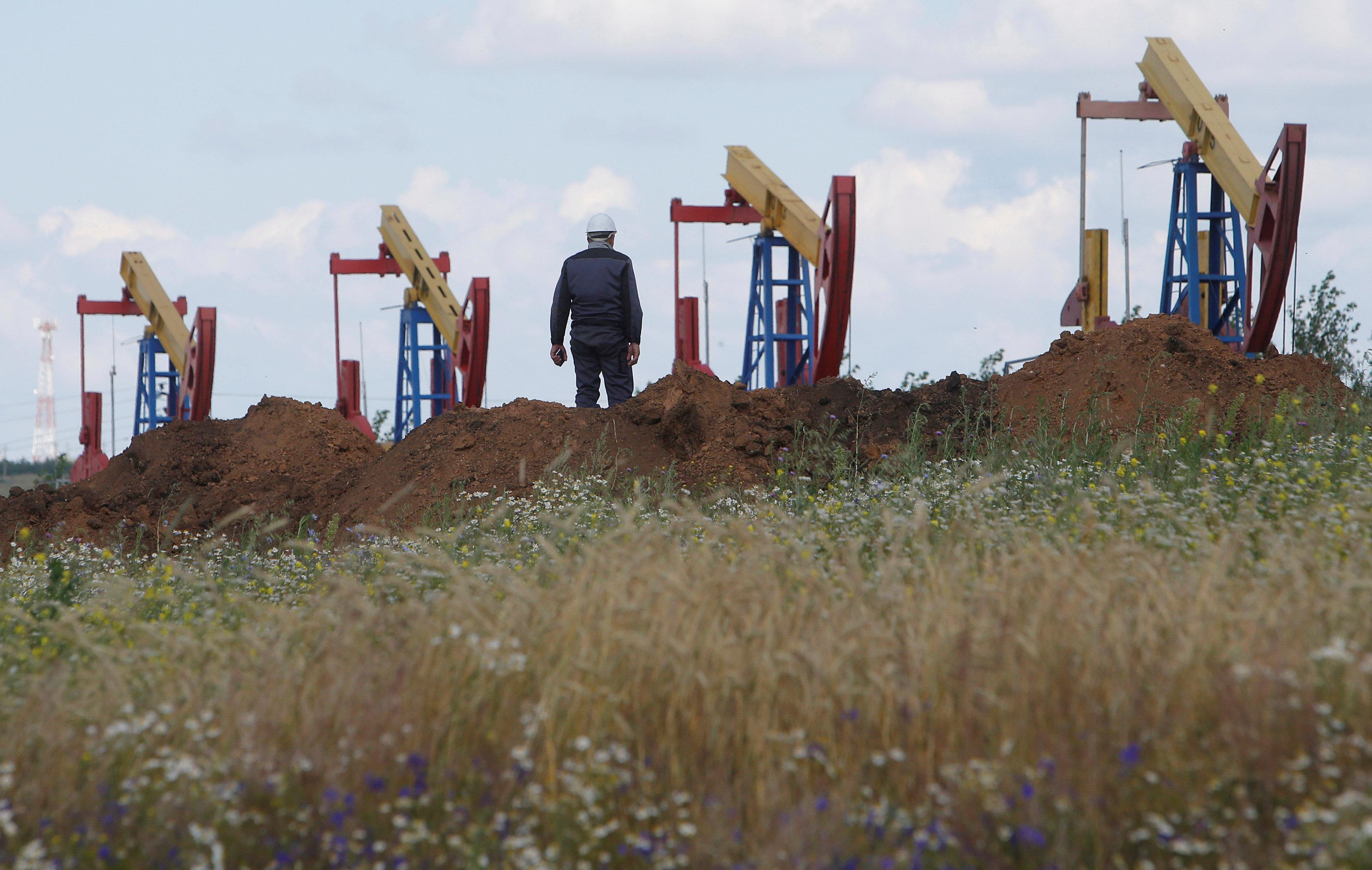 A worker stands in front of pump jacks at the Ashalchinskoye oil field owned by Russia's oil producer Tatneft near Almetyevsk, in the Republic of Tatarstan, Russia July 27, 2017. Sergei Karpukhin