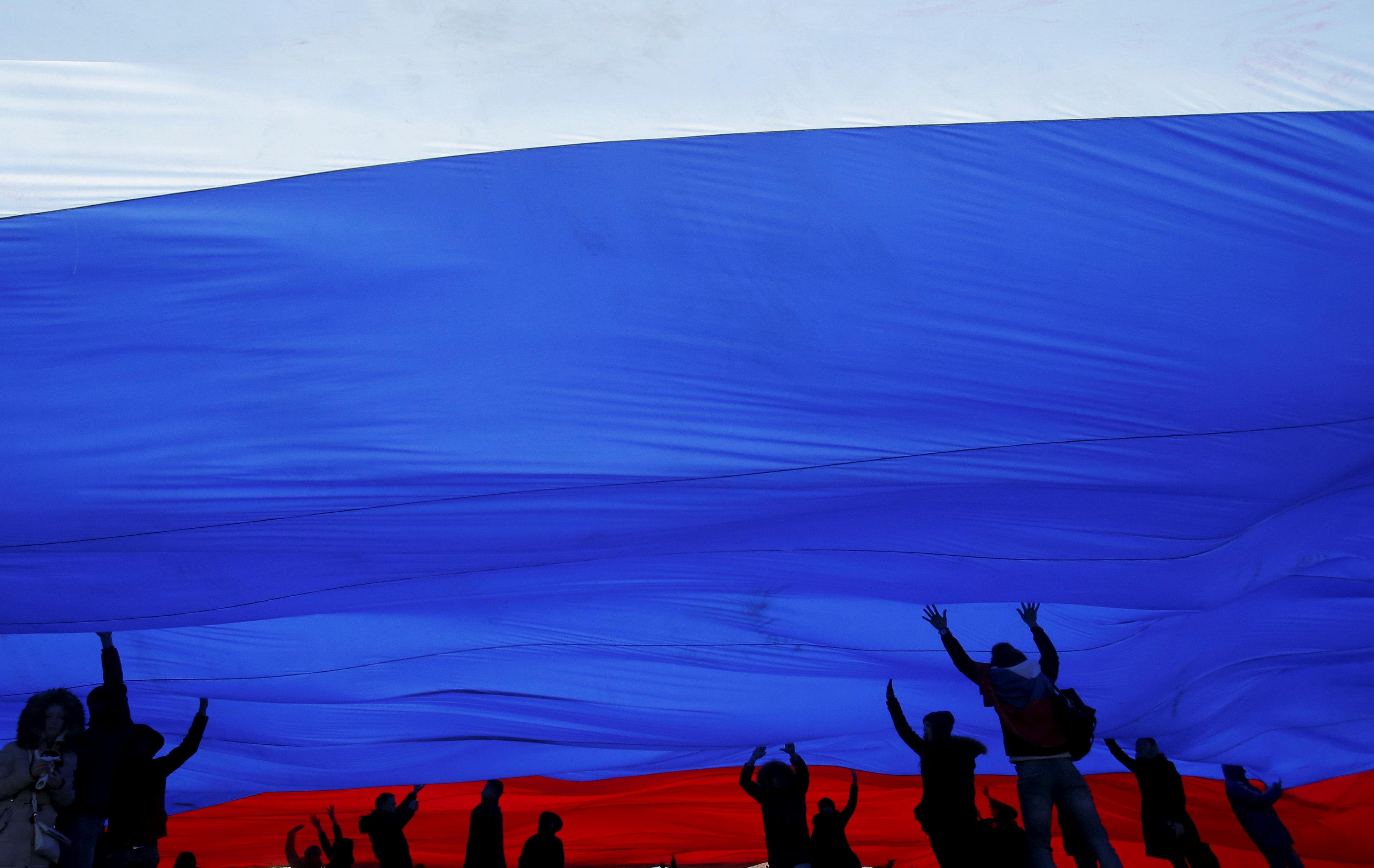 People hold a giant Russian national flag during a festive concert marking the second anniversary of Russia's annexation of the Crimea region, in Red Square in central Moscow, Russia March 18, 2016.  Maxim Shemetov