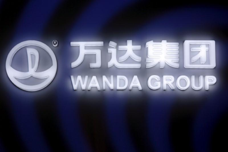 A sign of Dalian Wanda Group in China glows during an event in Beijing, China March 21, 2016. Damir Sagolj