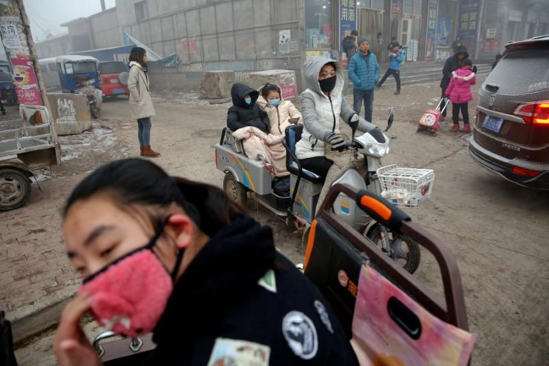 People wear face masks as heavy smog blankets Shenfang in Hebei province, on an very polluted day December 20, 2016.   Damir Sagolj