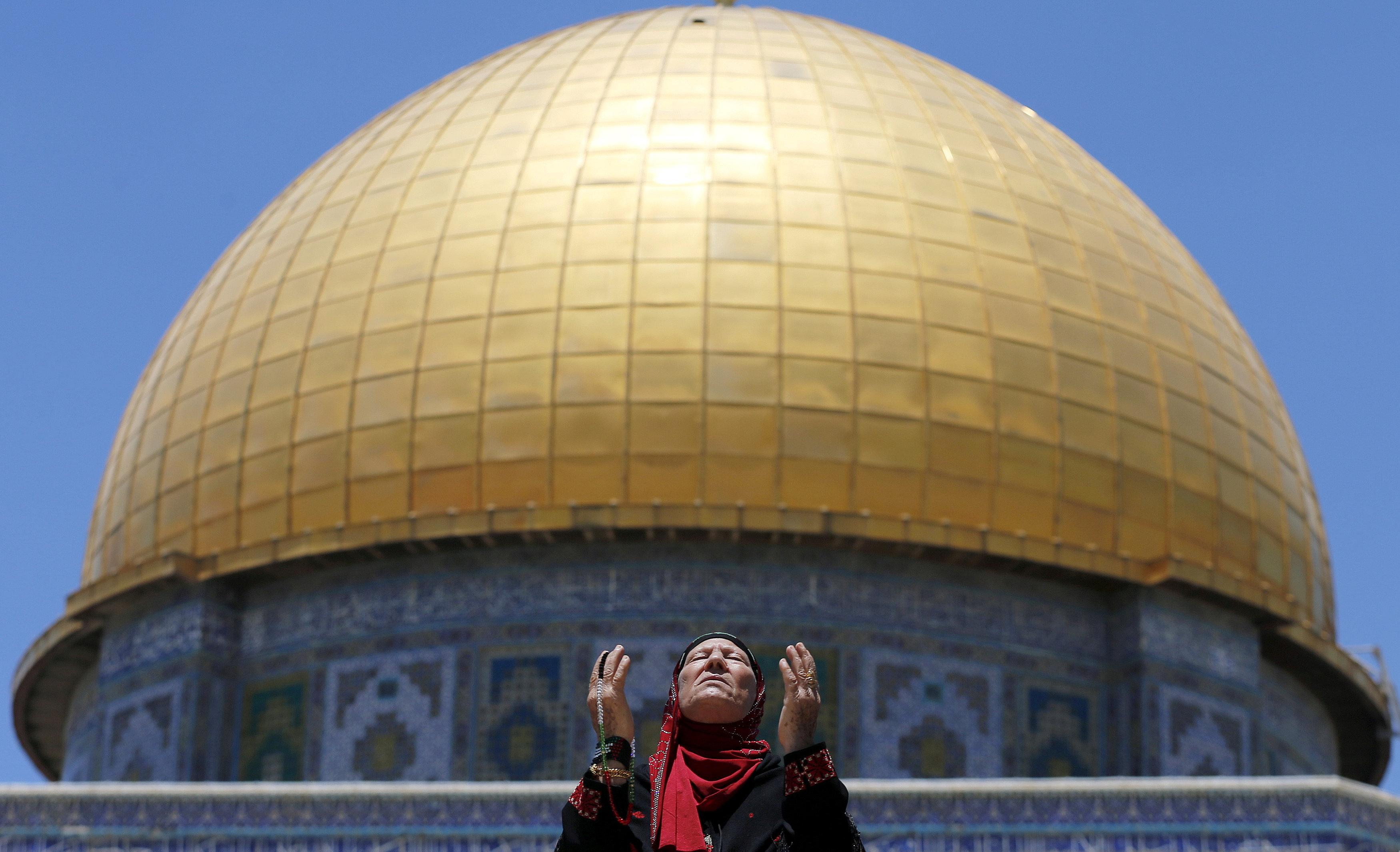 A Palestinian woman prays in front of the Dome of the Rock on the first Friday of the holy month of Ramadan at the compound known to Muslims as the Noble Sanctuary and to Jews as Temple Mount, in Jerusalem's Old City June 19, 2015. Ammar Awad