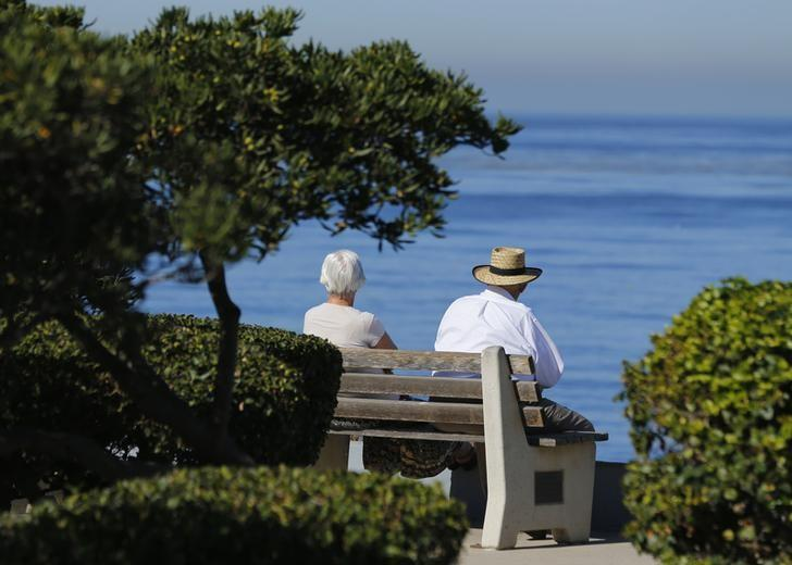 An elderly couple looks out at the ocean as they sit on a park bench in La Jolla, California November 13, 2013. Mike Blake