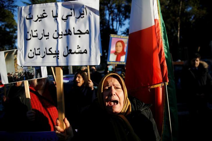 Opponents of Iranian President Hassan Rouhani hold a protest outside the Iranian embassy in Rome, Italy, January 2, 2018. The placard says: