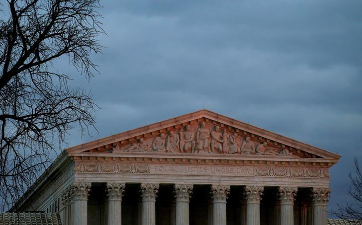 The top of U.S. Supreme Court building is lit at dusk in Washington, U.S., December 18, 2017.   Joshua Roberts