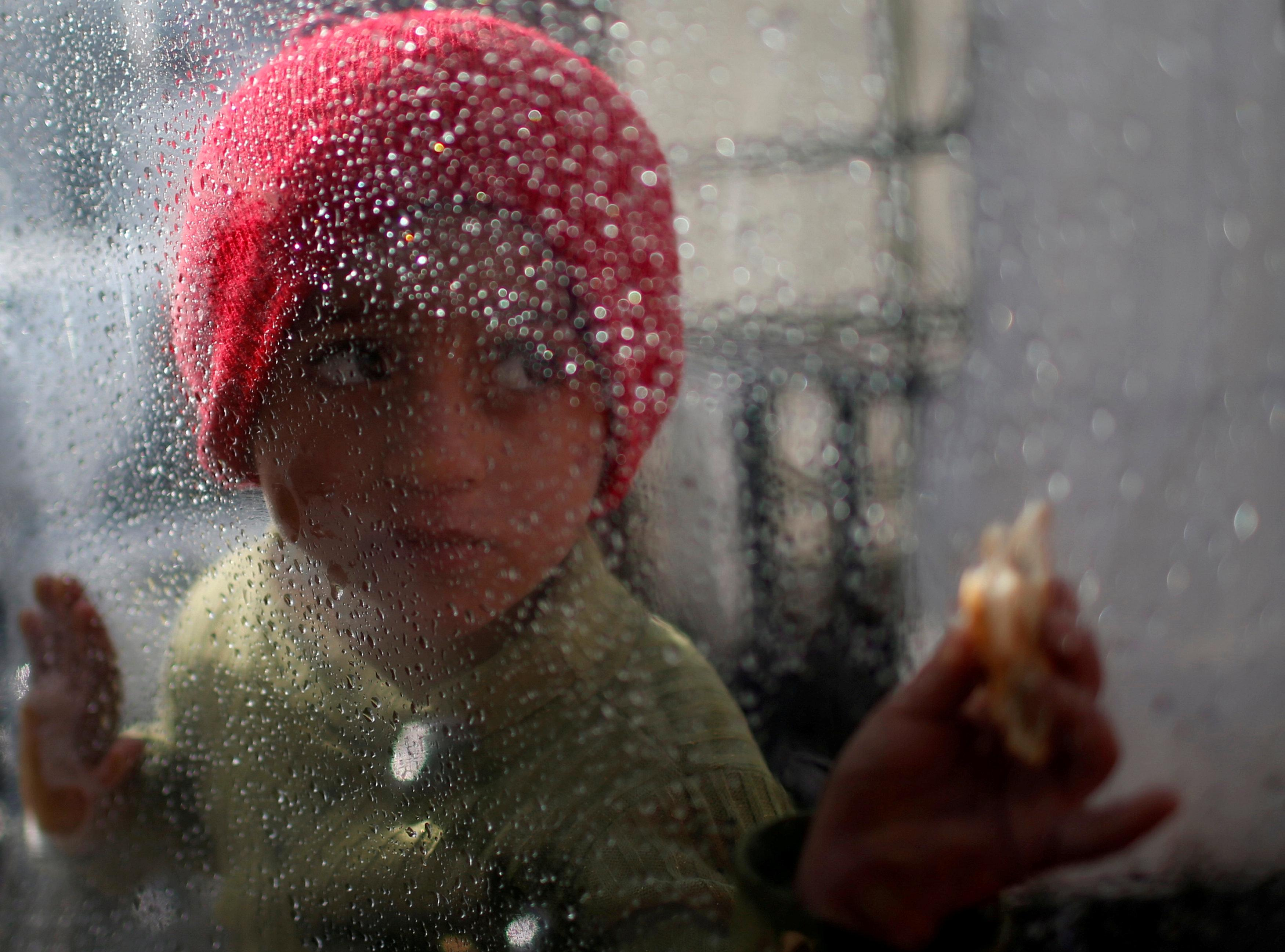 A Palestinian girl looks through a plastic sheet as raindrops are seen, outside her family's house in Al-Shati refugee camp in Gaza City January 17, 2018. Mohammed Salem