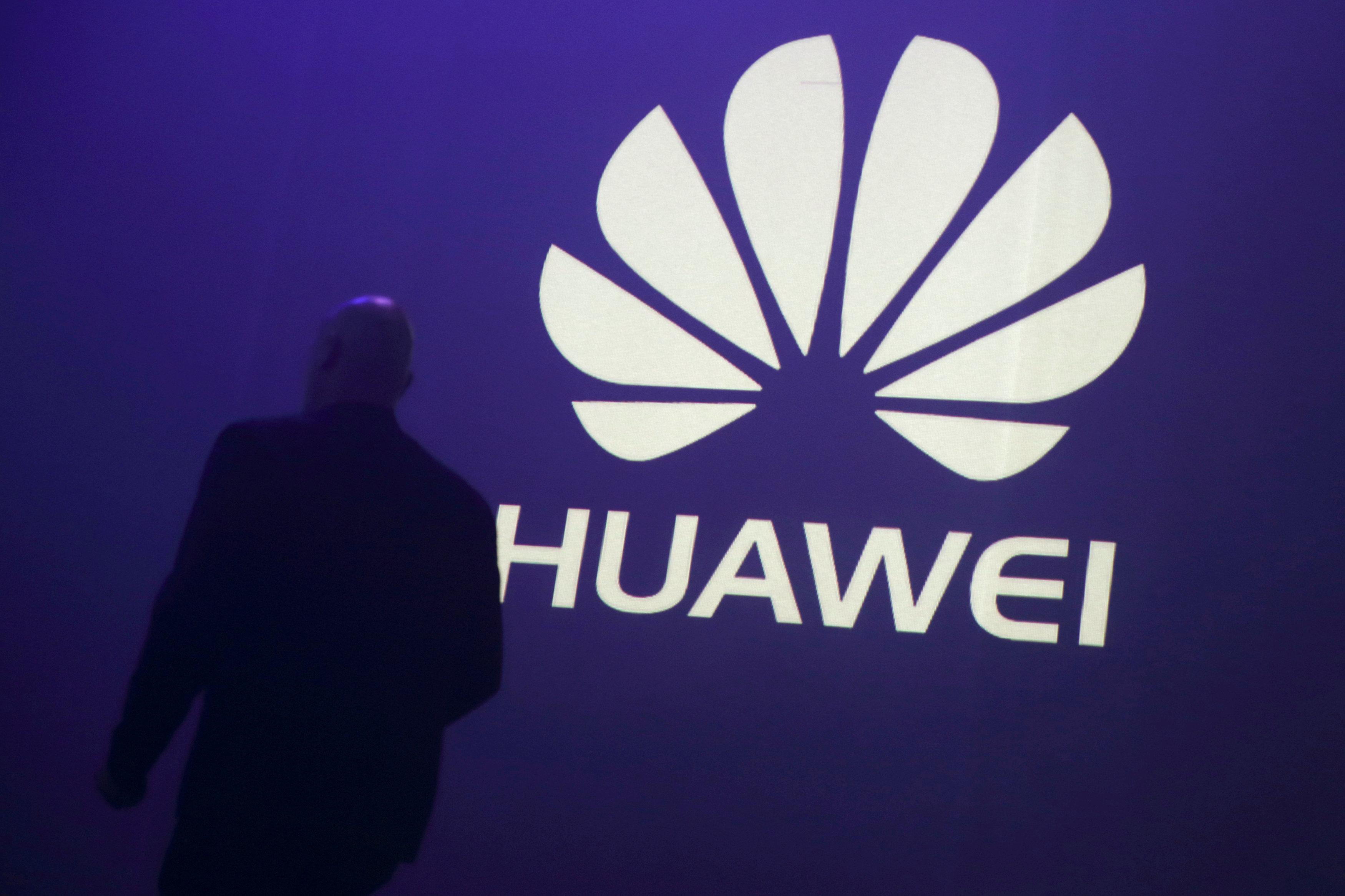 A man walks past a logo during the presentation the Huawei's new smartphone, the Ascend P7, launched by China's Huawei Technologies in Paris, May 7, 2014.  Philippe Wojazer