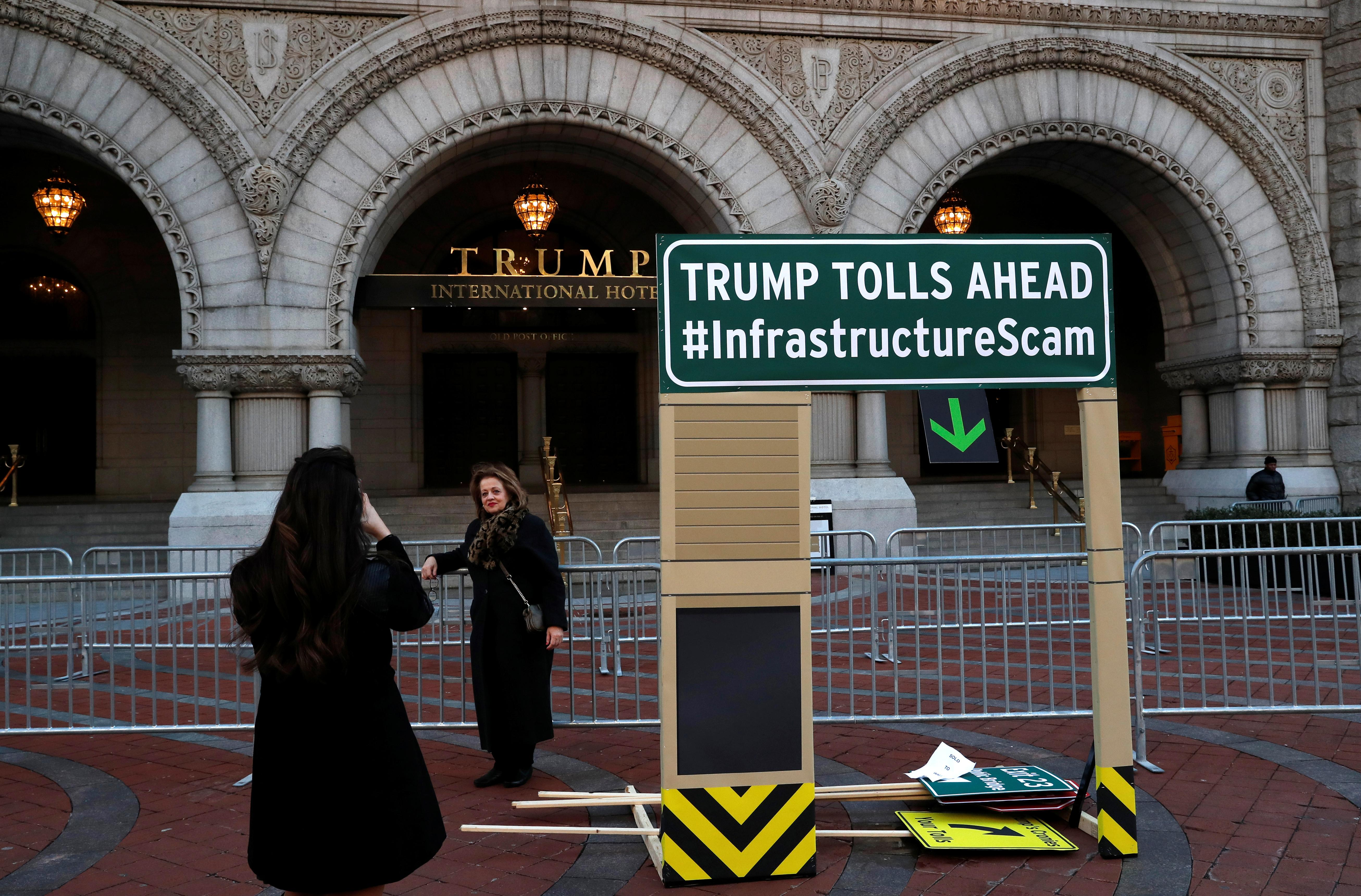 Pedestrians take photographs with Trump International Hotel next to a backdrop leftover from a protest against U.S. President Donald Trump's recently unveiled infrastructure plan in Washington, U.S., February 12, 2018.  Leah Millis