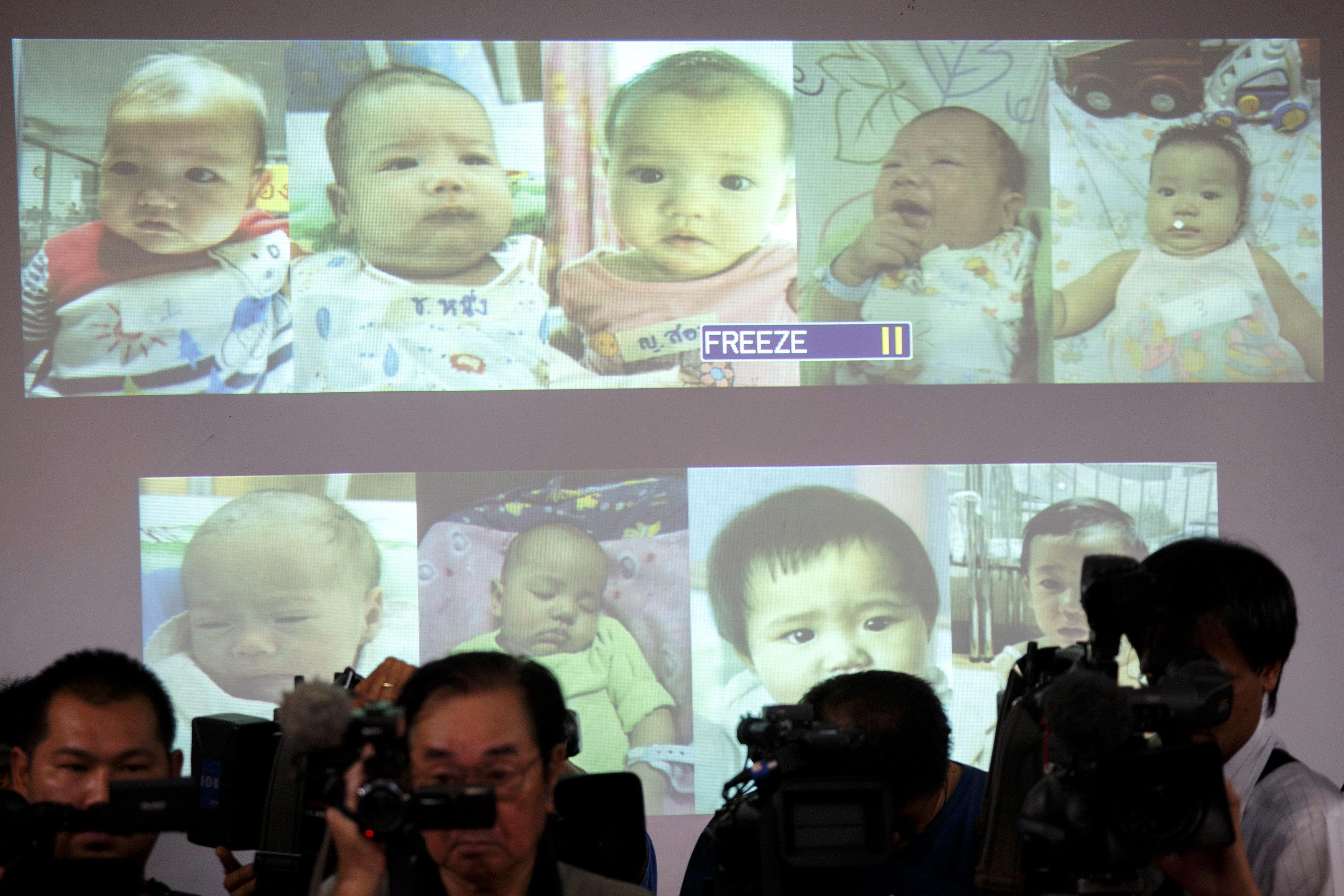 Surrogate babies that Thai police suspect were fathered by a Japanese businessman who has fled from Thailand are shown on a screen during a news conference at the headquarters of the Royal Thai Police in Bangkok August 12, 2014. Athit Perawongmetha