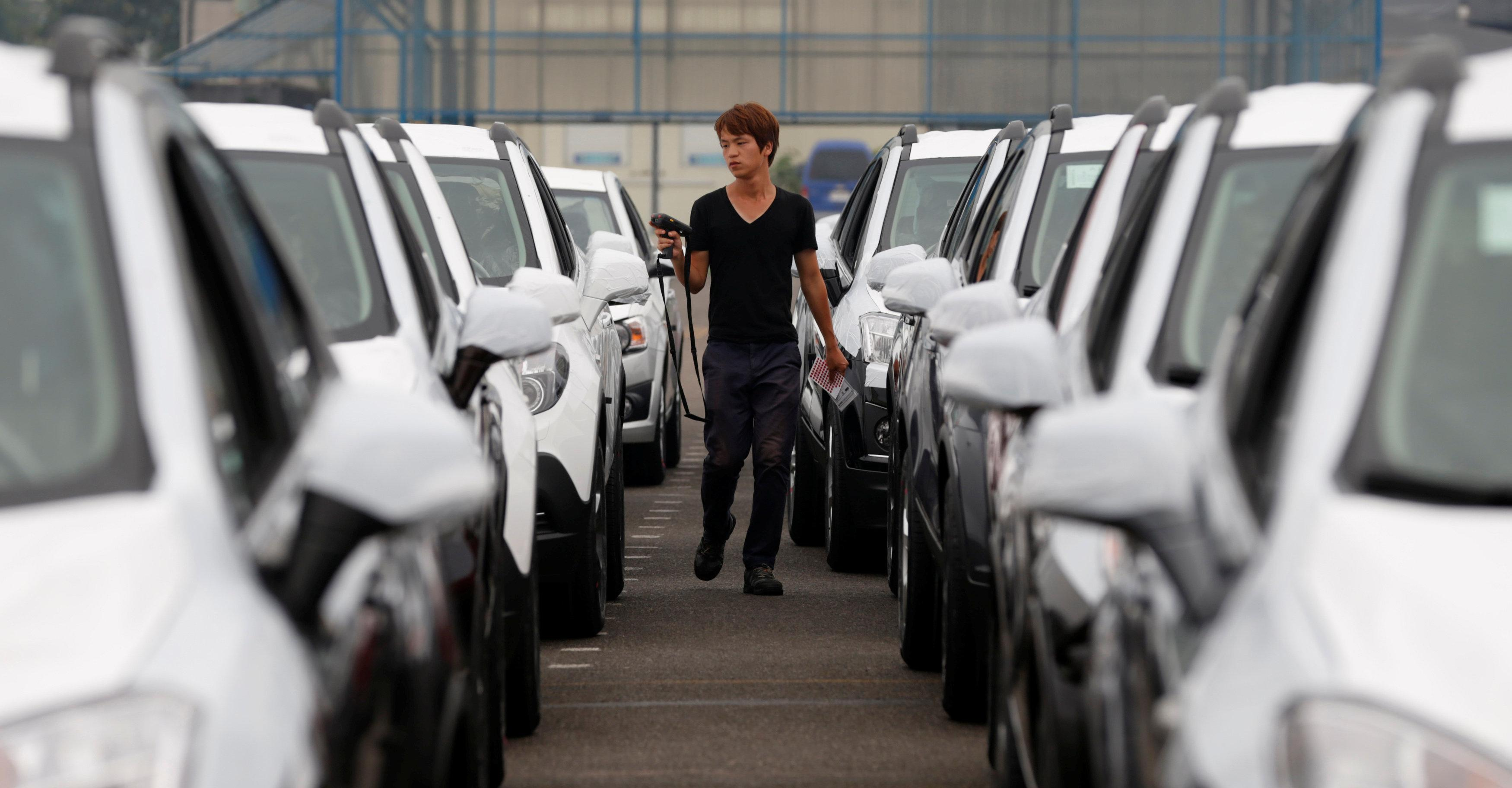 A worker checks cars made by GM Korea in a yard of GM Korea's Bupyeong plant before they are transported to a port for export, in Incheon, west of Seoul August 9, 2013.  Lee Jae-Won