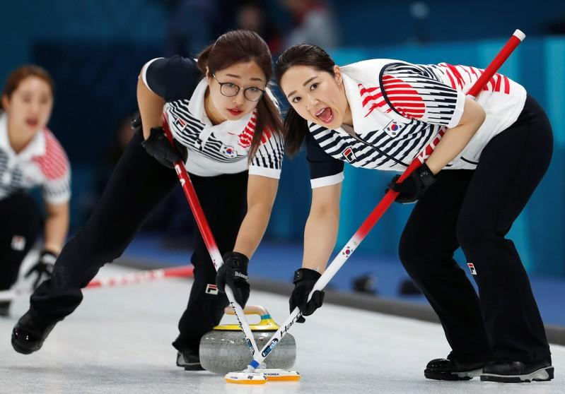 Curling - Pyeongchang 2018 Winter Olympics - Women's Round Robin - Canada v South Korea - Gangneung Curling Center - Gangneung, South Korea - February 15, 2018 - Kim Kyeong-ae and Kim Seo-yeong of South Korea sweep. Cathal McNaughton