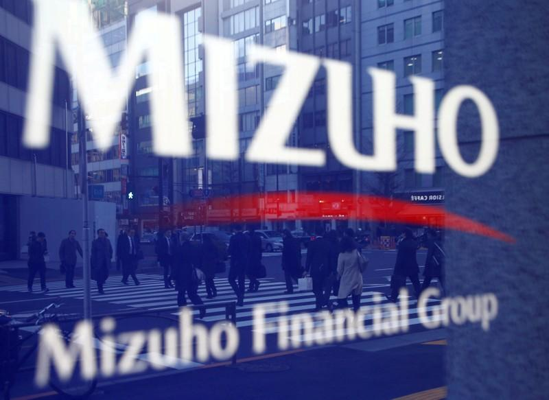 Pedestrians are reflected on Mizuho Bank's signboard in Tokyo, Japan, January 25, 2017. Kim Kyung-Hoon