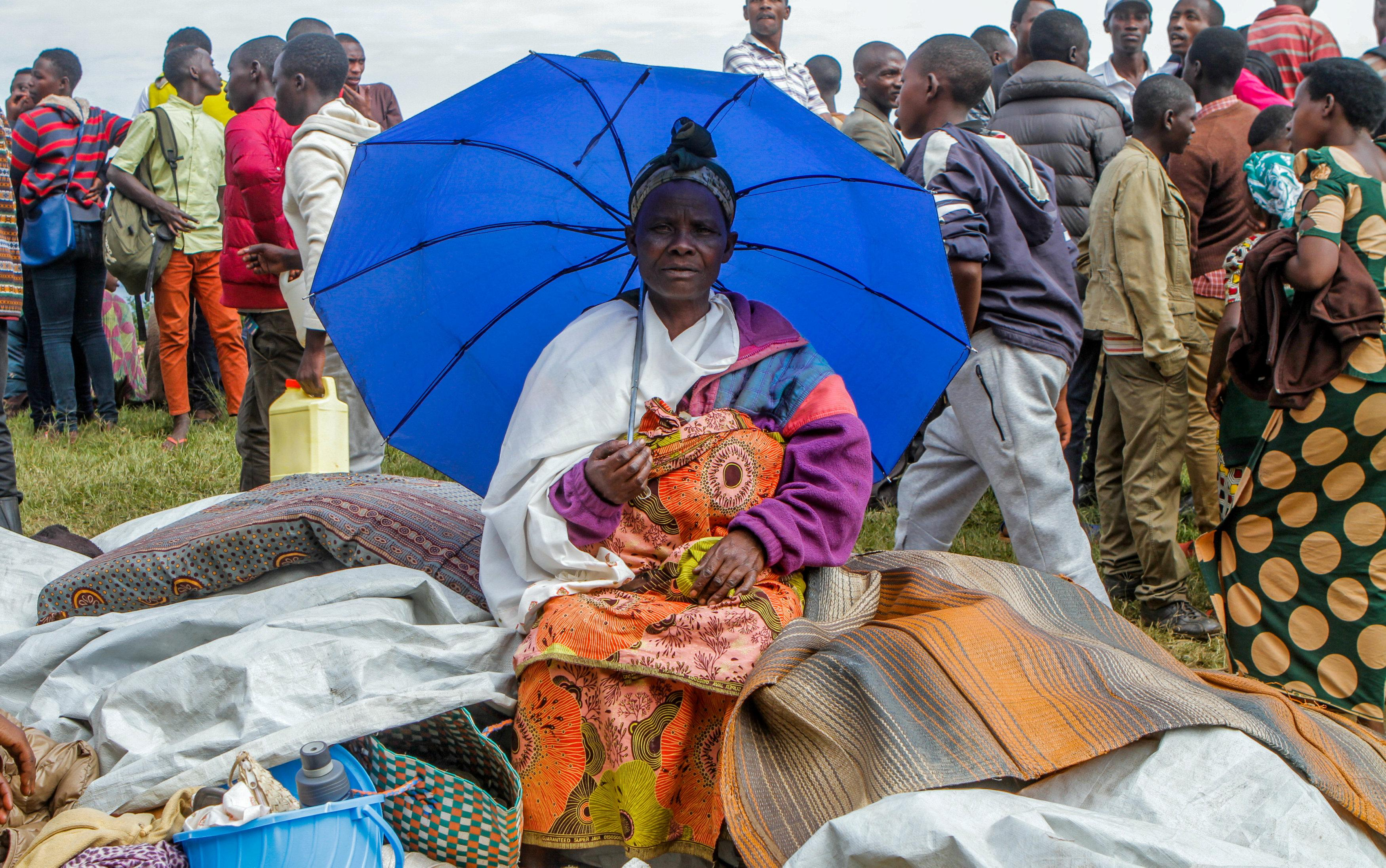 A refugee from the Democratic Republic of Congo sits with her belongings near the United Nations High Commissioner for Refugees (UNHCR) offices in Kiziba refugee camp in Karongi District, Rwanda February 21, 2018. Jean Bizimana