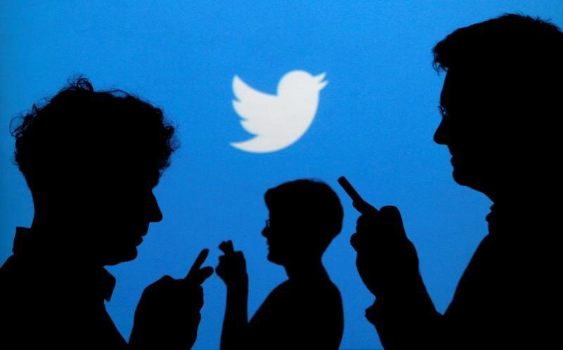 People holding mobile phones are silhouetted against a backdrop projected with the Twitter logo in this illustration picture taken in  Warsaw September 27, 2013.   Kacper Pempel/Illustration