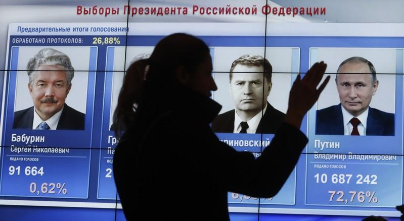 A woman stands in front of a screen showing preliminary election results at the headquarters of Russia's Central Election Commission in Moscow, March 18, 2018. Vladimir Putin won Sergei Karpukhin