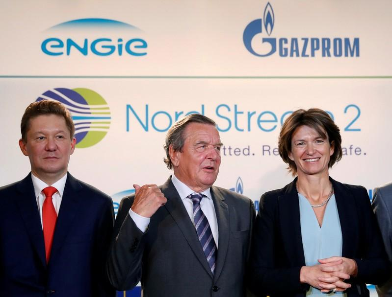Gazprom chief Alexei Miller (L) poses with former German Chancellor Gerhard Schroeder (C) and Isabelle Kocher, Chief Executive Officer of French gas and power group Engie, pose in Paris, France, April 24, 2017, after western partners of gas giant Gazprom agreed on Monday on financing the 9.5-billion euro ($10.32 billion) Nord Stream 2 pipeline.   Christian Hartmann