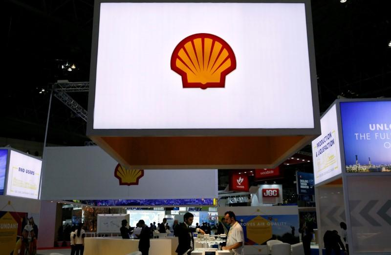 Staff members work at the booth of Royal Dutch Shell at Gastech, the world