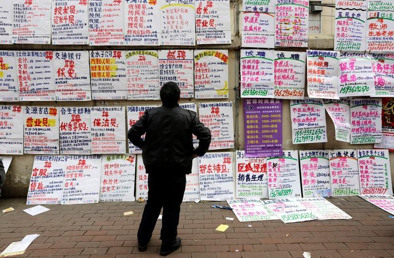 A man looks at job information at an employment fair beside a street in Zhengzhou, Henan province, February 19, 2014. Jason Lee