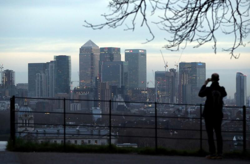 A man takes a photograph of the Canary Wharf financial district from Greenwich Park in London, Britain, January 22, 2017. Hannah McKay