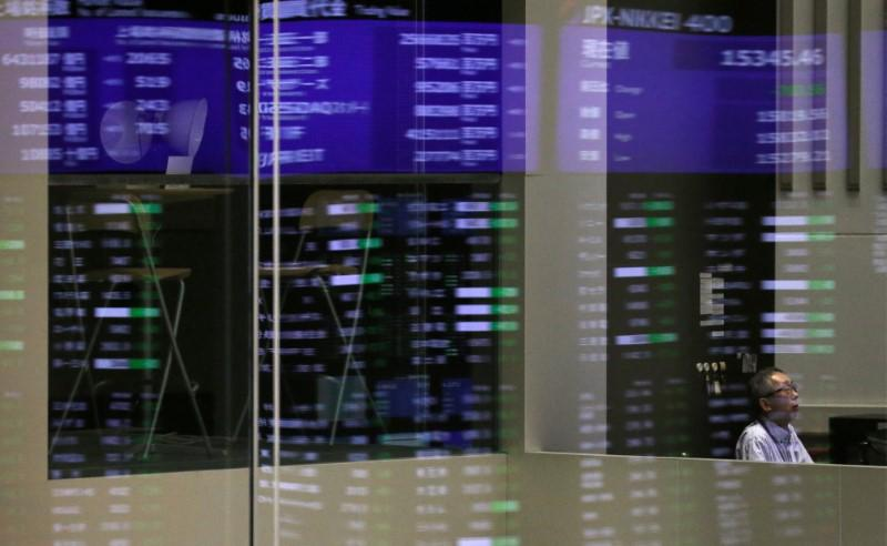 Market prices are reflected in a glass window at the Tokyo Stock Exchange (TSE) in Tokyo, Japan, February 6, 2018.  Toru Hanai