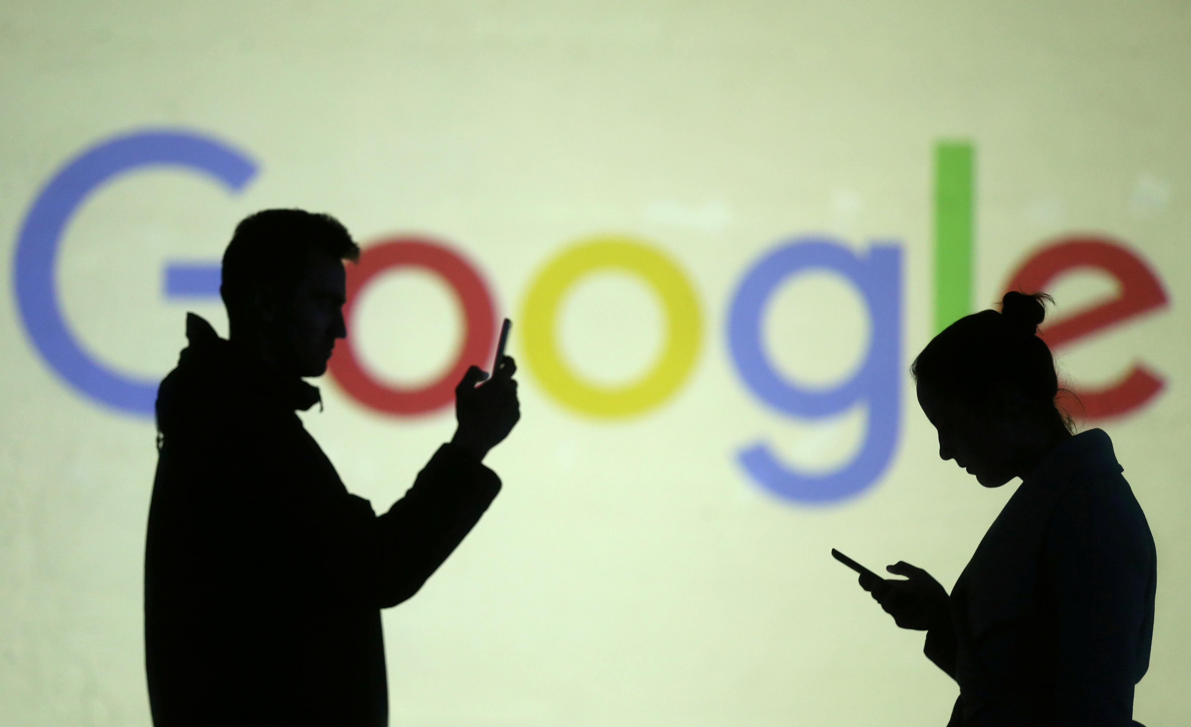 Silhouettes of mobile users are seen next to a screen projection of Google logo in this picture illustration taken March 28, 2018.  Dado Ruvic/Illustration