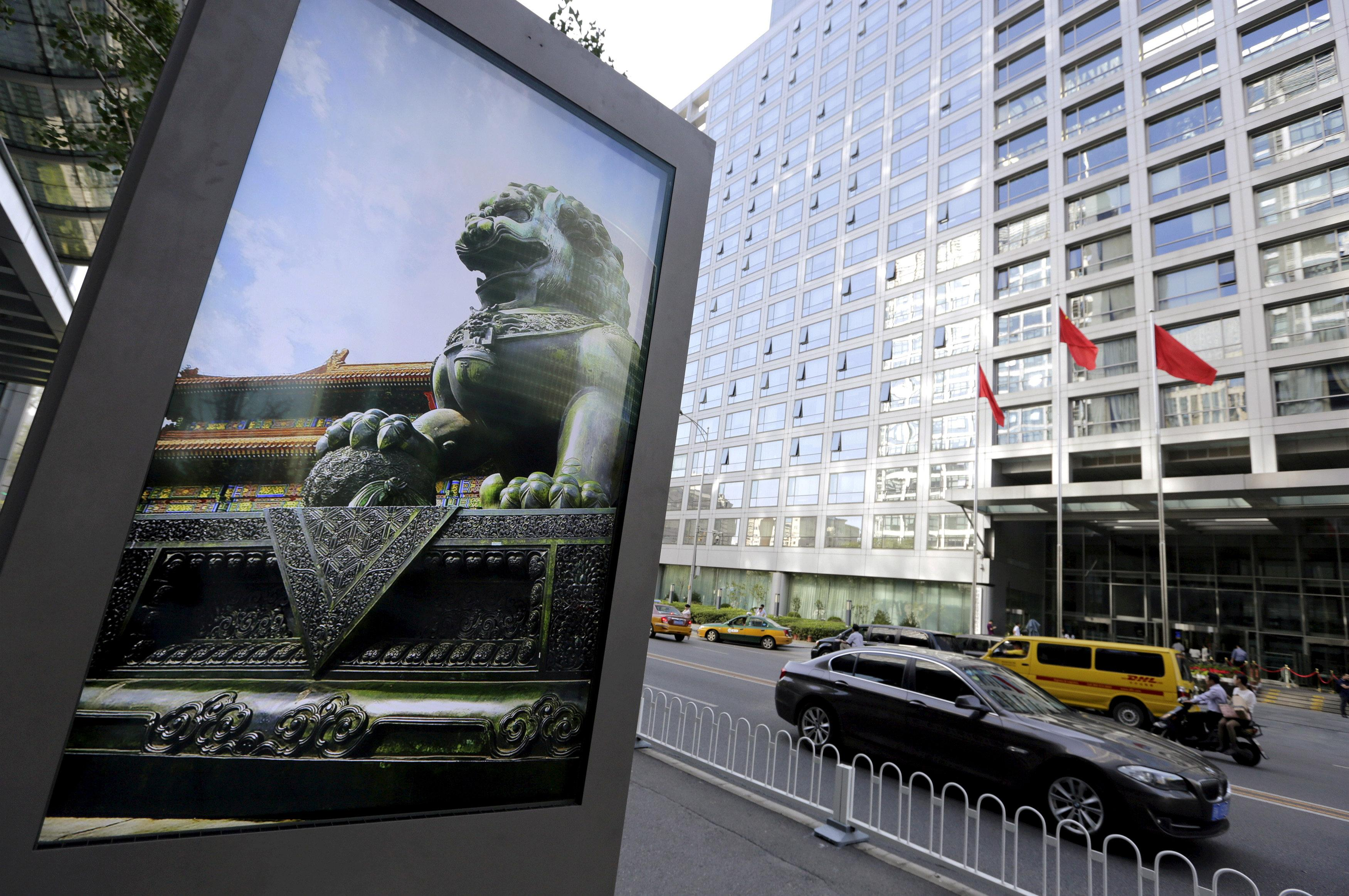 An advertising board (L) showing a Chinese stone lion is pictured near an entrance to the headquarters (R) of China Securities Regulatory Commission (CSRC), in Beijing, China, September 7, 2015. Jason Lee