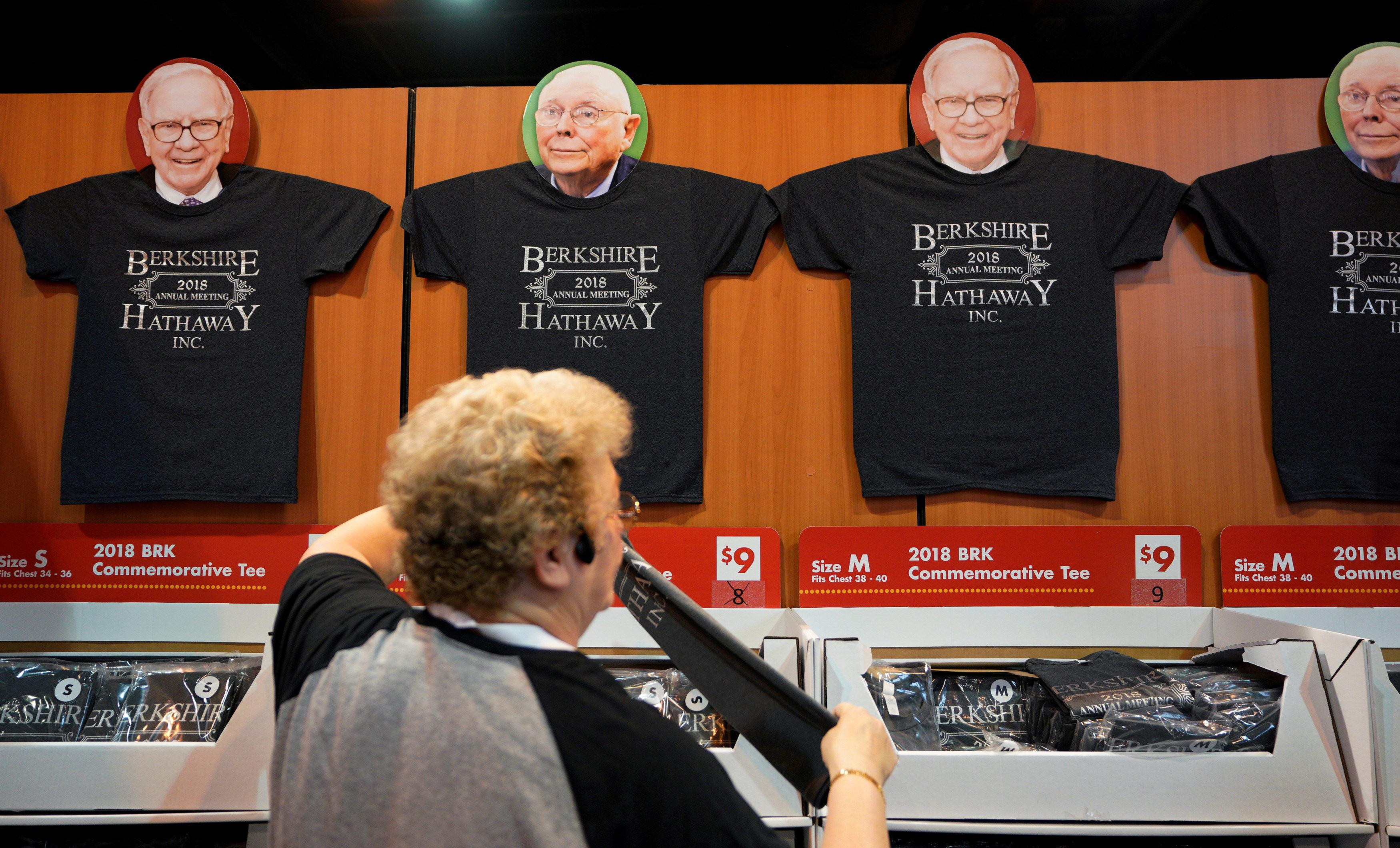 A worker arranges a display of t-shirts with images of Warren Buffett and Charlie Munger at the Berkshire Hathaway Inc annual meeting, the largest in corporate America, in its hometown of Omaha, Nebraska, U.S., May 4, 2018. Rick Wilking