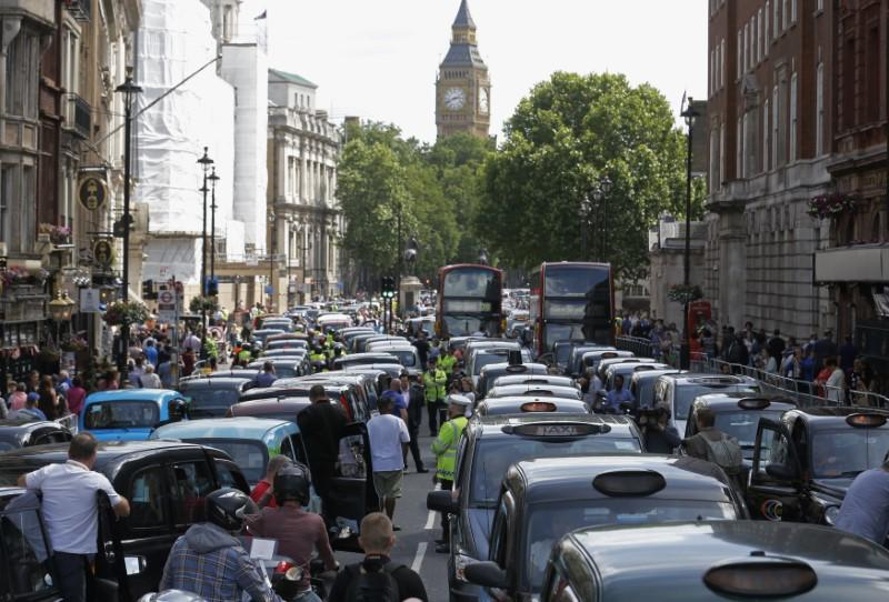 Taxi drivers block the road in Whitehall in central London June 11, 2014. Taxi drivers sowed traffic chaos in Europe's top cities on Wednesday by mounting one of the biggest ever protests against Uber, a U.S. car service which allows people to summon rides at the touch of a button. Luke MacGregor