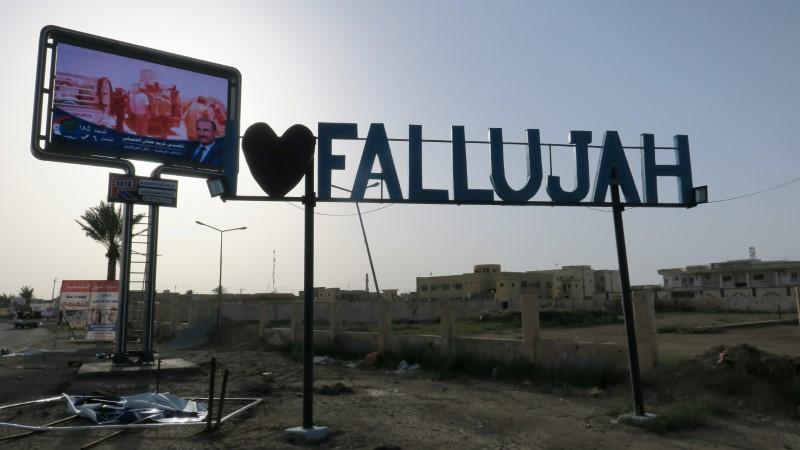 A candidate's poster lies on the ground near an 'I love Fallujah' sign during the Iraqi parliamentary election, May 12, 2018. Ahmed Aboulenein