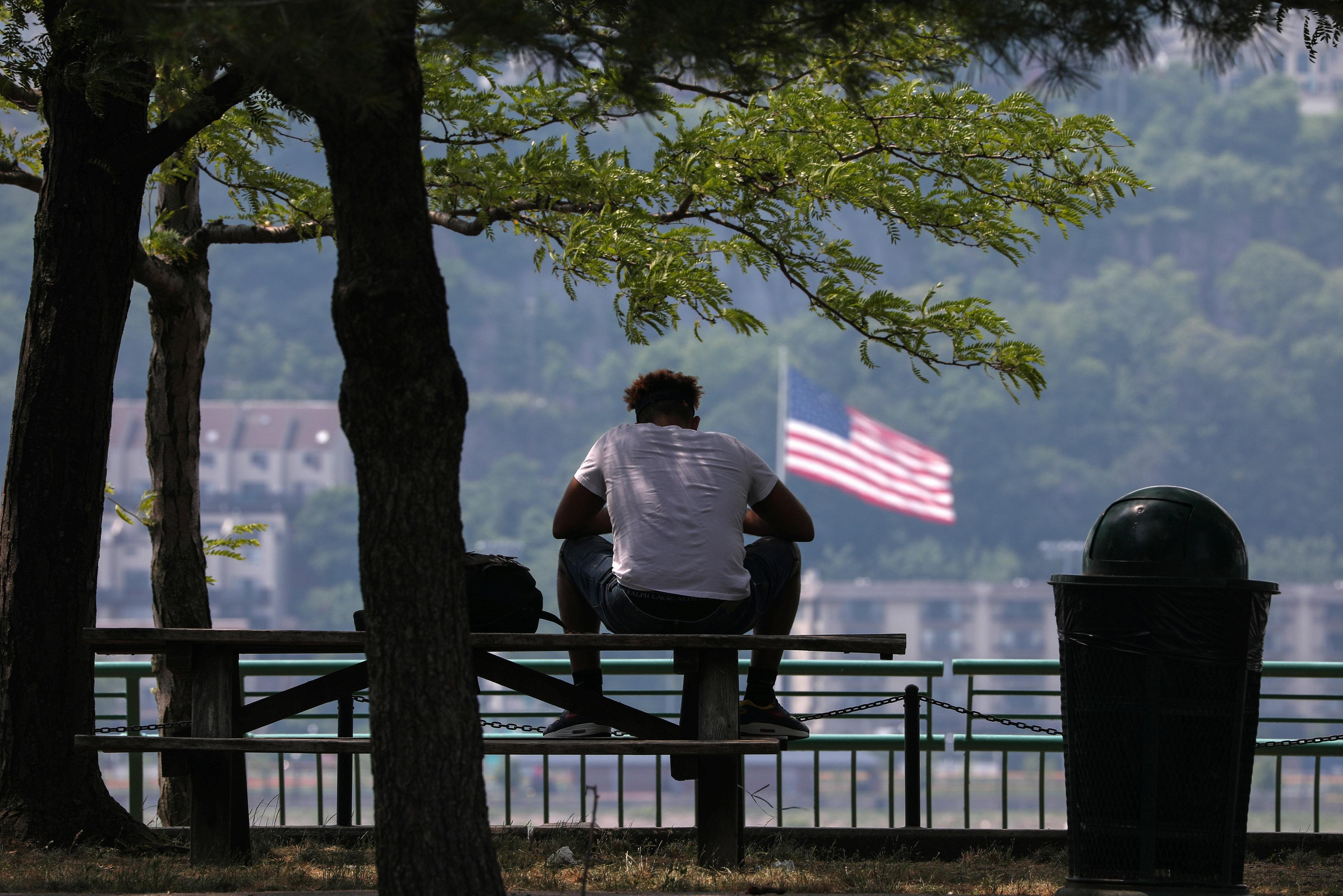 A man sits in the shade at Riverbank State Park during very hot weather in the Washington Heights section of Manhattan in New York City, New York, U.S., June 18, 2018. Mike Segar