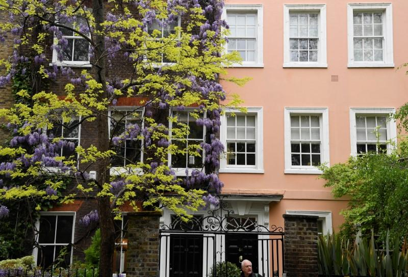 A man walks past the exterior of a house covered in blooming wisteria in west London, Britain, April 28, 2018. Toby Melville