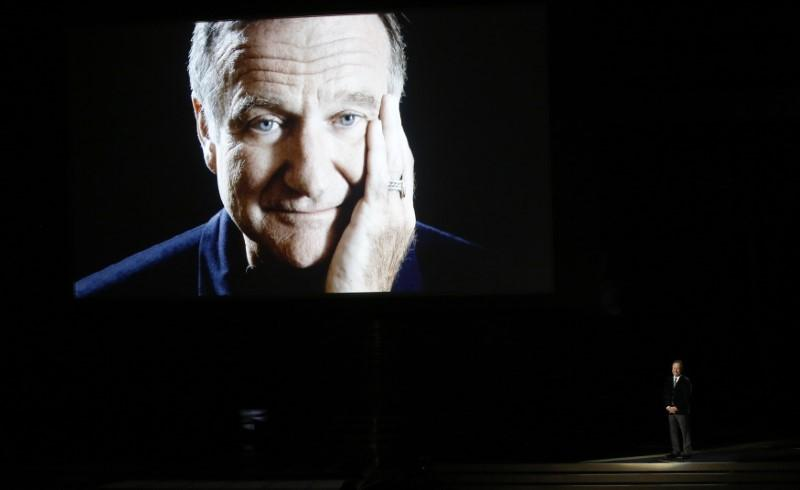 Billy Crystal takes the stage to pay tribute to the late Robin Williams, shown on a large screen, during the 66th Primetime Emmy Awards in Los Angeles, California August 25, 2014.   Mario Anzuoni