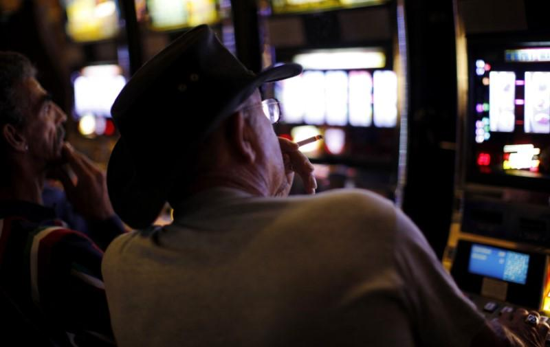 A man smokes as he plays a slot machine at the Island View Casino in Gulfport, Mississippi November 9, 2009. Carlos Barria