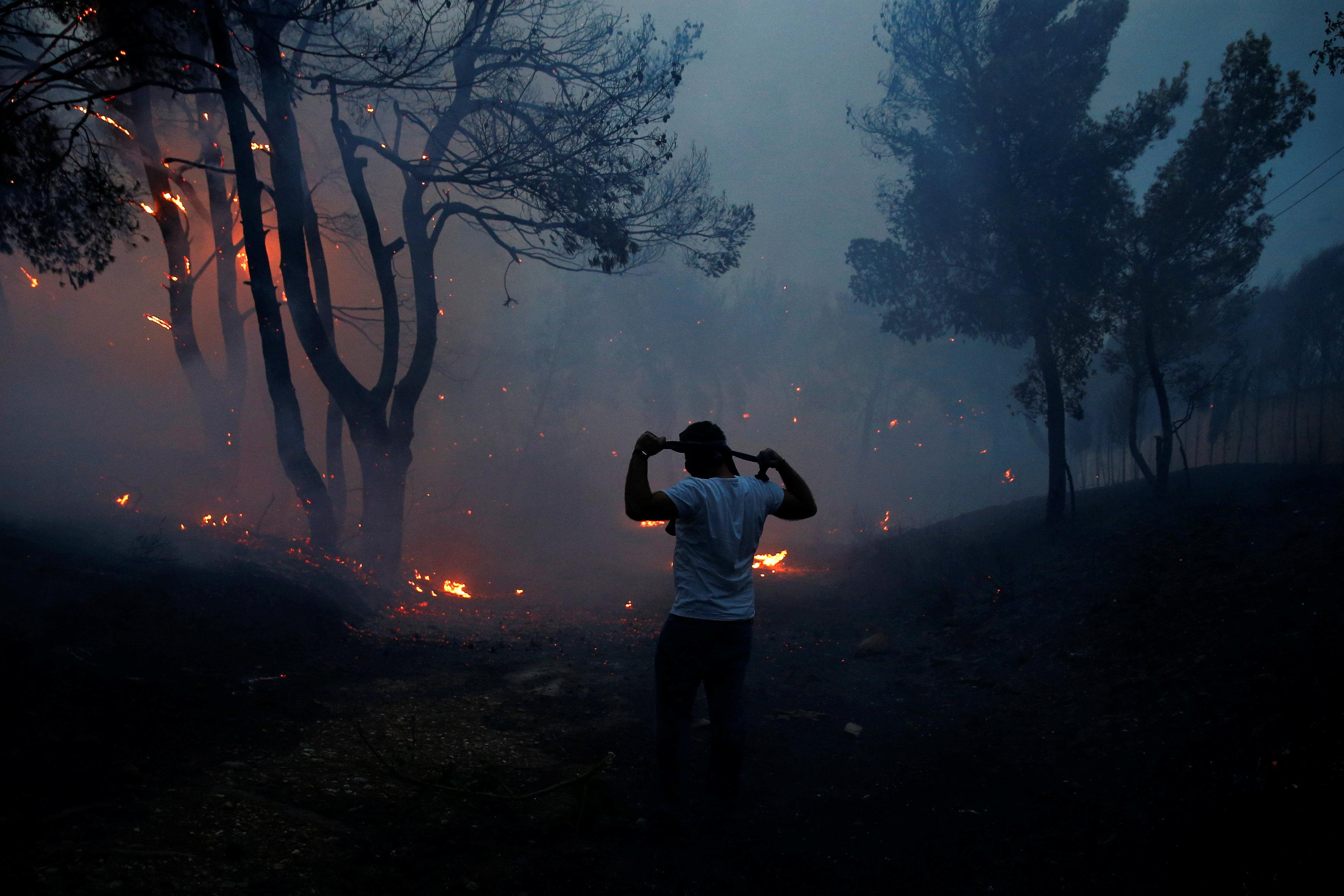 A man uses a cloth to protect himself from smoke as wildfire burns in the town of Rafina, near Athens, Greece, July 23, 2018. Costas Baltas
