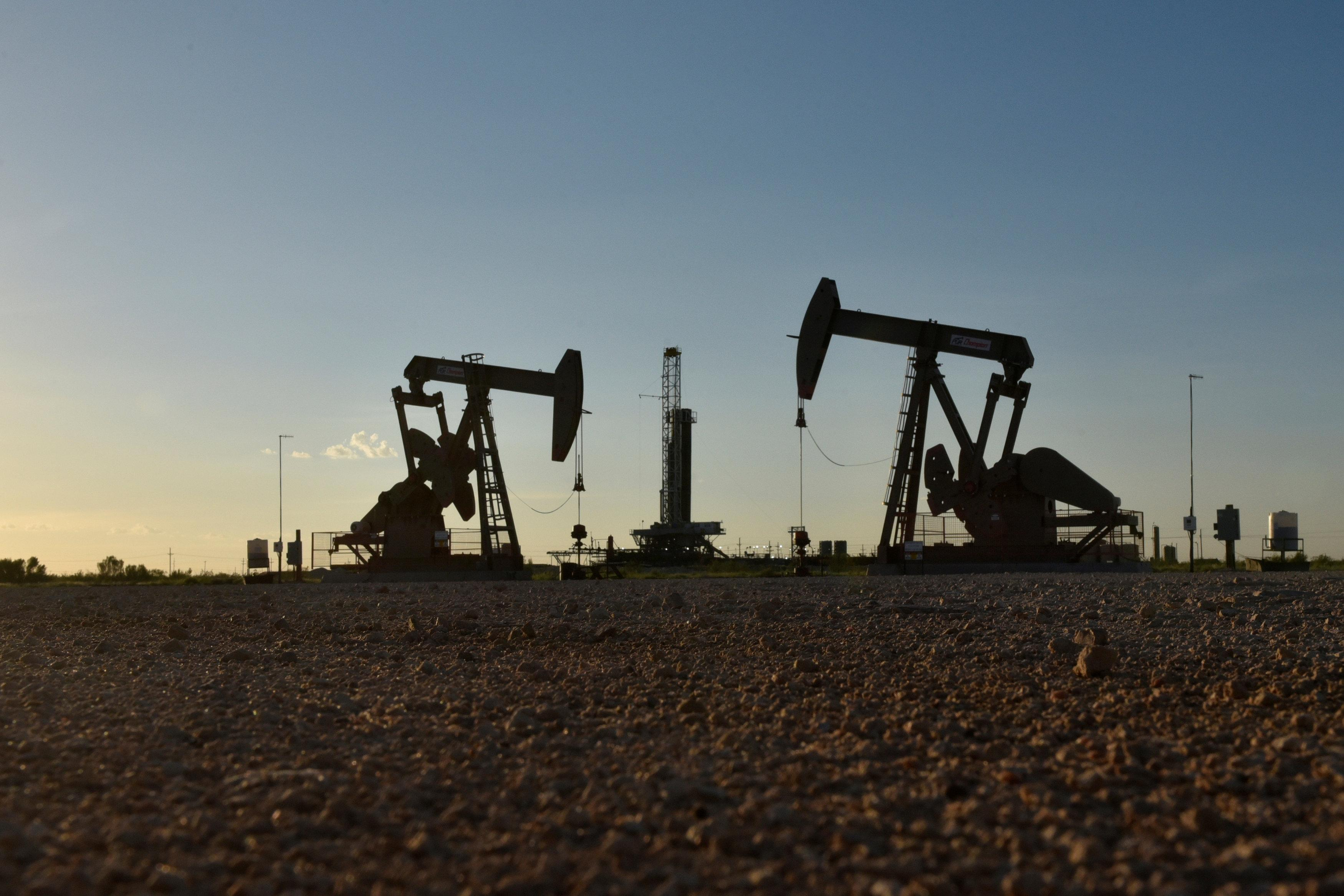 Pump jacks operate in front of a drilling rig in an oil field in Midland, Texas U.S. August 22, 2018. Nick Oxford