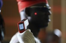 A man has his temperature taken using an infrared digital laser thermometer at the Nnamdi Azikiwe International Airport in Abuja, August 11, 2014.  Nigeria's commercial capital Lagos has 10 confirmed cases of Ebola, up from seven at the last count, and two patients have died, including the Liberian who brought the virus in, the health minister said on Monday. REUTERS/Afolabi Sotunde (NIGERIA - Tags: HEALTH DISASTER TPX IMAGES OF THE DAY) - RTR42131