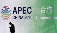 A man walks past a wall bearing a logo of the 2014 Asia Pacific Economic Cooperation (APEC) at the venue for APEC CEO Summit while its opening ceremony is being held in Beijing November 9, 2014. China's economy is stable and the risks that it faces are not that scary, President Xi Jinping said on Sunday in a speech at the APEC CEO Summit. REUTERS/Kim Kyung-Hoon (CHINA - Tags: POLITICS) - RTR4DE3T