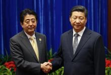 China's President Xi Jinping (R) shakes hands with Japan's Prime Minister Shinzo Abe during their meeting at the Great Hall of the People, on the sidelines of the Asia Pacific Economic Cooperation (APEC) meetings, in Beijing November 10, 2014. Xi and Abe held formal talks on Monday for the first time since the two leaders took office, a breakthrough in ending a two-year row between Asia's biggest economies over history and territory. REUTERS/Kim Kyung-Hoon (CHINA - Tags: POLITICS BUSINESS) - RTR4DI5M