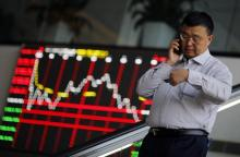 A man talks on the phone inside the Shanghai Stock Exchange building at the Pudong financial district in Shanghai November 17, 2014. International buyers snapped up Chinese stocks on Monday at the debut of an exchange link that allows Hong Kong and Shanghai investors to trade shares on each other's bourses, a major step towards opening China's tightly controlled capital markets. The so-called Stock Connect scheme gives foreign and Chinese retail investors unprecedented access to the two exchanges, which some analysts said could eventually lead to the creation of the world's third largest stock exchange. REUTERS/Carlos Barria  (CHINA - Tags: BUSINESS) - RTR4EEAO