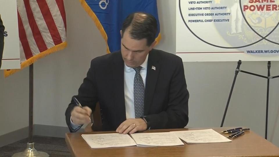 Walker signs power grab bills, Evers not happy