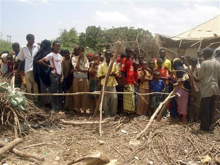 Residents of Afgooye settlement, 30 Km south of Mogadishu, stand outside a house destroyed by an explosion, March 16, 2007. REUTERS/Shabelle Media