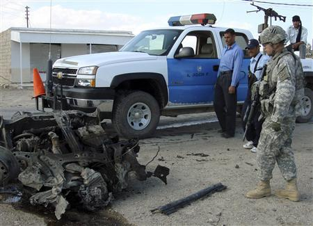 A U.S. soldier and Iraqi police inspect the wreckage of a vehicle used in a car bomb attack in Ramadi, March 27, 2007. REUTERS/Stringer