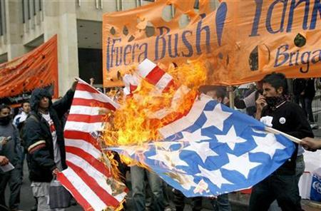 Demonstrators burn a replica of a U.S. flag after the arrival of President Bush in Bogota, Colombia, March 11, 2007. The United States' image is plummeting in many corners of the globe, but China and other large powers are falling from favor as well, according to a global survey released on Wednesday. REUTERS/Daniel Munoz